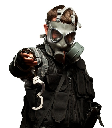 prisoner of war: Soldier With  A Gas Mask Holding Handcuffs On White Background Stock Photo