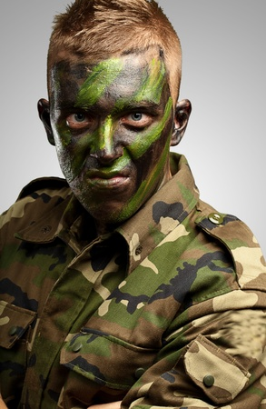 Close Up Of Angry Soldier against a grey background photo