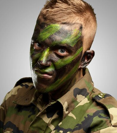 portrait of a soldier with camouflage painting against a grey background photo