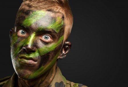 closeup of angry soldier with painting against a black background photo