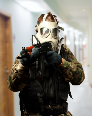 Portrait Of A Soldier With Gas Mask Aiming With Gun in a passage way photo