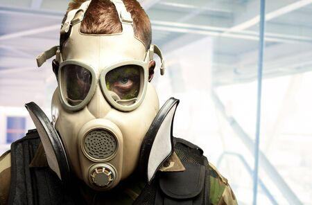 Close-up Of Soldier Wearing Mask against an abstract background, indoor photo