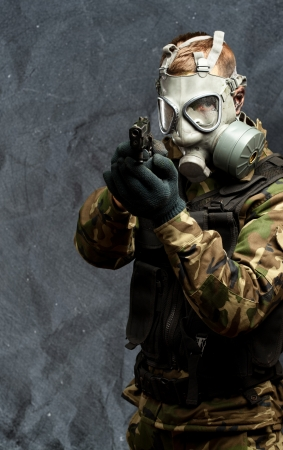 Portrait Of A Soldier With Gas Mask Aiming With Gun against a grunge background photo
