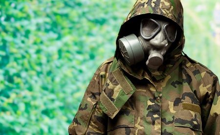angry soldier wearing a gas mask against a nature background photo