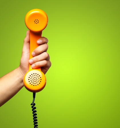 telefono antico: Primo piano della mano azienda telefono contro uno sfondo verde Archivio Fotografico