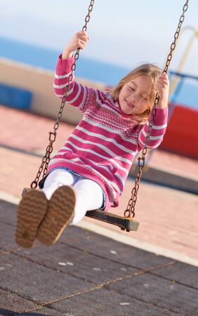 Happy Blonde Girl Swinging In Playground, Outdoors  photo