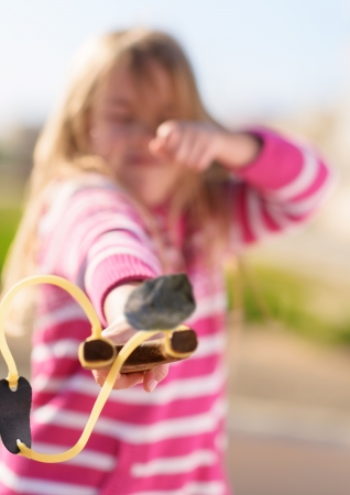 Blonde Girl Aiming With A Sling Shot, Outdoors Stock Photo - 18943619