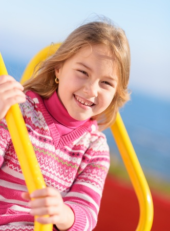 Little Blonde Girl Playing On Slide, Outdoors  photo