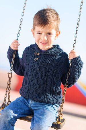 Little Boy Swinging In Playground  photo