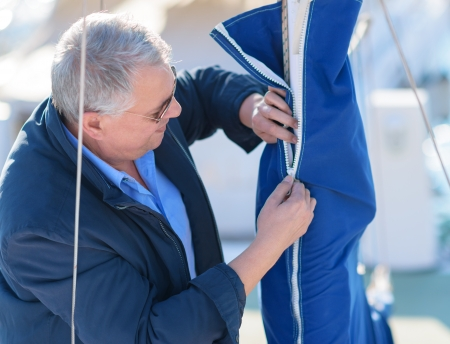 Mature Man Opening Sailboat Mast, Outdoors  photo