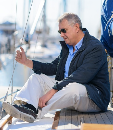 Mature Man Sitting On Sailboat, Outdoors  photo