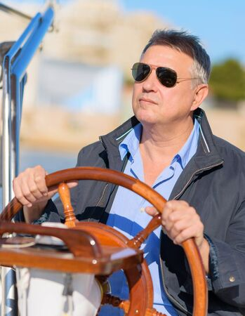 Mature Man Holding Steering Wheel Of Sailboat, Outdoors  photo