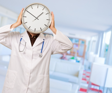Portrait Of Doctor Hiding Face With Clock, Indoors photo