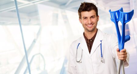 crouches: Young Doctor Holding Crouches, Indoors