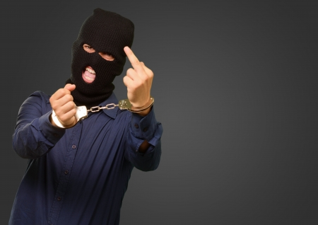 angry criminal man locked in handcuffs isolated on background Stock Photo - 18827845
