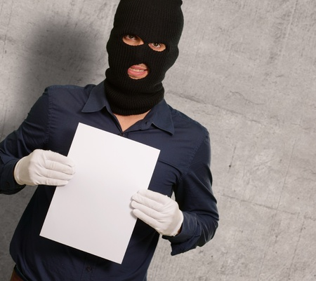 Man wearing a robber mask showing a blank paper, indoor photo