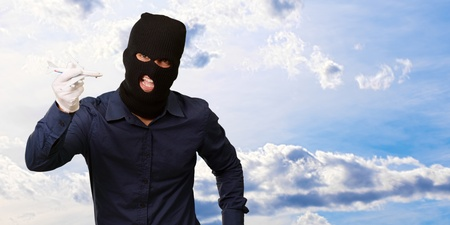 thievery: Man wearing robber mask and holding airplane miniature, outdoor Stock Photo