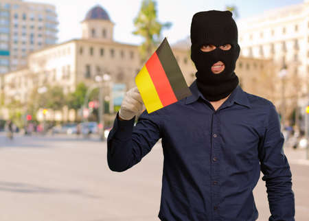 thievery: Man wearing robber mask and holding flag, outdoor