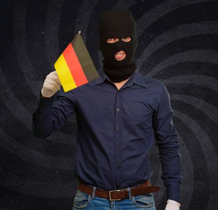 thievery: Man wearing robber mask and holding flag, indoor