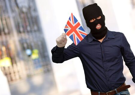 thievery: Portrait of a man wearing mask holding a flag, outdoor