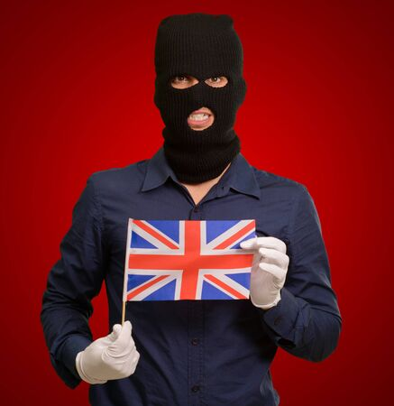 thievery: Portrait of a man wearing mask holding a flag isolated on red background Stock Photo