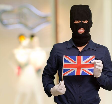 Portrait of a man wearing mask holding a flag, indoor photo