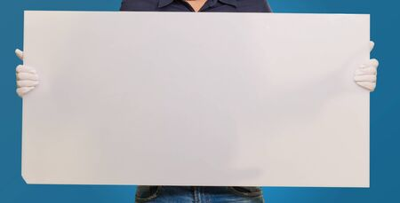 Man wearing mask holding a blank card isolated on blue background photo