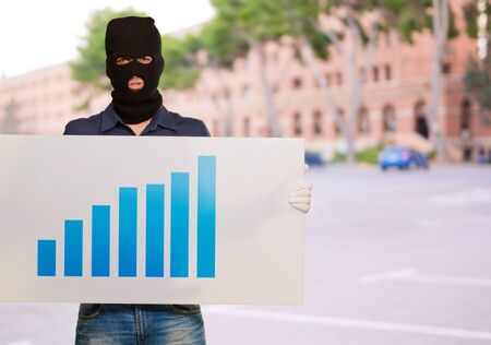 housebreaker: Man wearing mask holding a graph card, outdoor Stock Photo