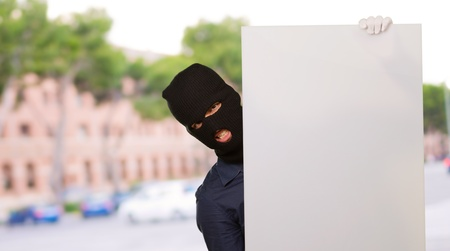 trespasser: Burglar Man Holding Blank Placard, Outdoors Stock Photo