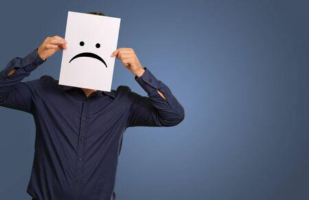 caras tristes: Hombre que sostiene una tarjeta de papel con la cara aislada en el fondo azul