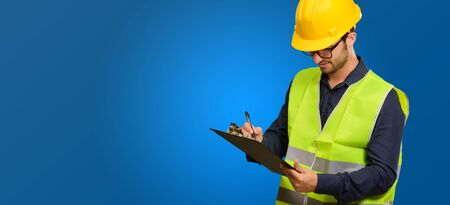 Young Engineer Writing On Writing Pad On Blue Background photo