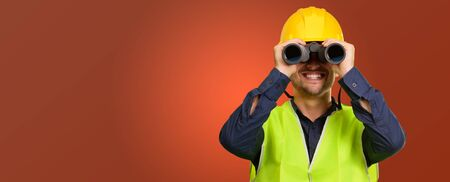 hard look: Young Engineer Looking Through Binoculars On Coloured Background