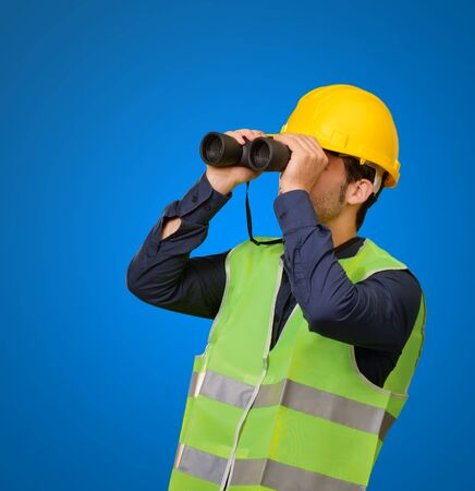 Young Engineer Looking Through Binoculars On Blue Background photo