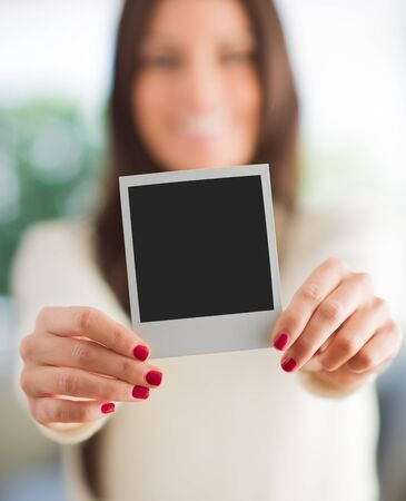 Woman Holding Blank Instant Photo, Indoors  photo
