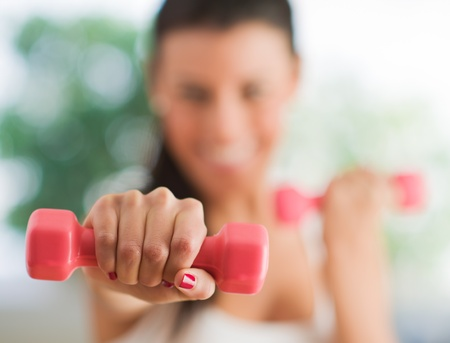 Woman Exercising With Dumbbells, Indoors  photo