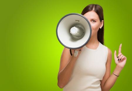 hablar en publico: Mujer joven que sostiene el megáfono contra un fondo verde Foto de archivo