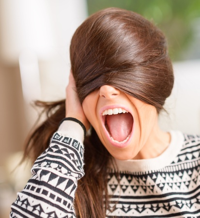 Angry Young Woman Hiding Face With Hair, Indoors