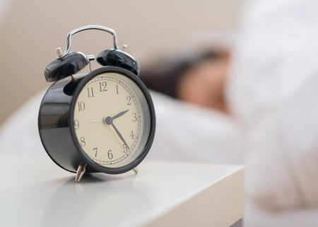 bedside: Alarm Clock In Front Of A Person Sleeping