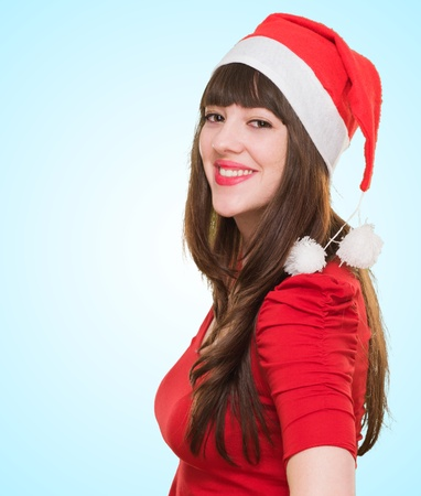 beautiful woman with a christmas hat against a blue background photo