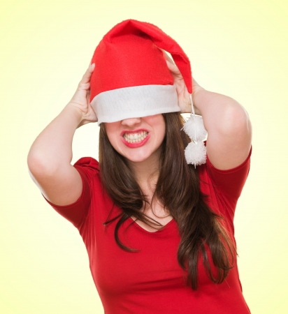angry woman with a christmas hat covering her eyes against a yellow background photo