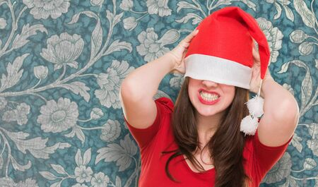 angry woman with a christmas hat covering her eyes against a vintage background photo