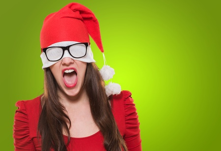 angry christmas woman with a hat and glasses covering her eyes against a green background photo