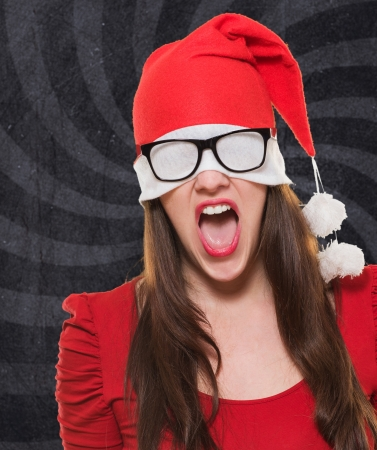 hiding face: angry christmas woman with a hat and glasses covering her eyes against a vintage background