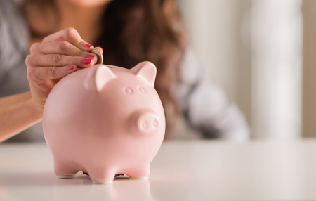Woman Putting Münze in Piggy Bank, Indoors