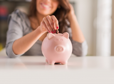 dropping: Woman Putting Coin In Piggy Bank, Indoors