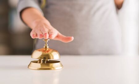 call bell: Close-up Of Womans Hand Ringing Service Bell  Stock Photo