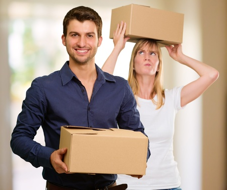 Young Couple Holding Cardboard Box photo