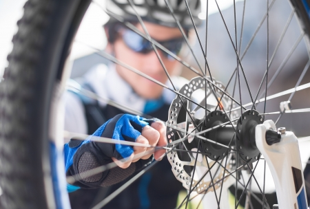 Young Man Repairing Bicycle Wheel; Outdoors Standard-Bild