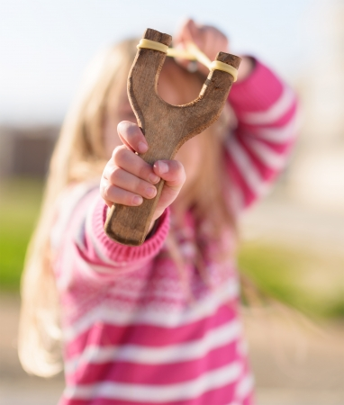 harass: Small Girl Aiming With A Sling Shot, Outdoors