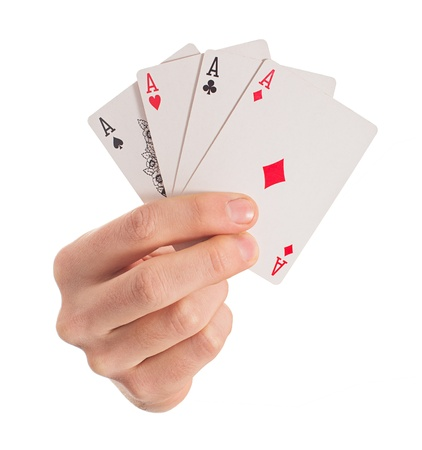 Close-up Of Hand Holding Four Aces On White Background Фото со стока
